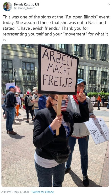 anti-lockdown protester holds a sign reading ARBEIT MACHT FREI